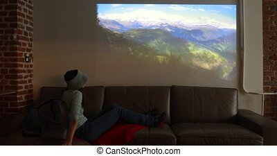 Woman imitates a walk in mountains while looking at projector during quarantine while sitting at home on sofa in room