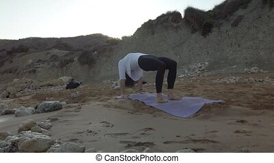 Woman in 40s practicing yoga on the sandy beach in early morning. High quality 4k footage