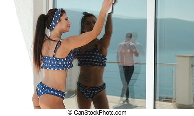 Woman in a bathing suit wiping window which man is reflected.