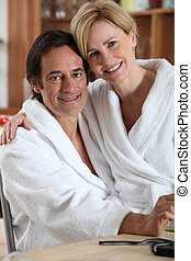 Woman in a bathrobe, sitting on her partner's lap