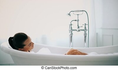 Woman in a bathtub - Hygiene. Beautiful girl in a bathtub