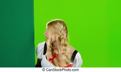 Girl in a bavarian costume looks out from behind a board and surprise covering her mouth with his hand, on oktoberfest, young woman in bavarian national costume shows the thumb and a finger beckons to herself, green screen