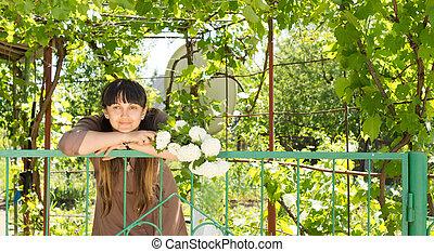 Woman in a beautiful leafy garden