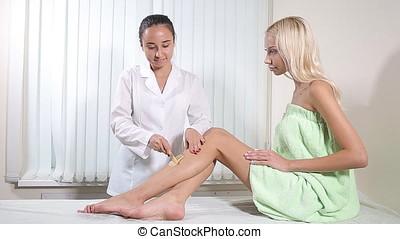 Woman In A Beauty Salon Doing Depilation. Wax depilation in...