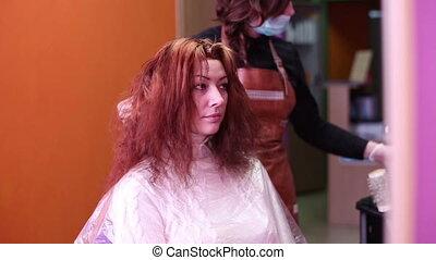 Woman in a beauty salon hair colors