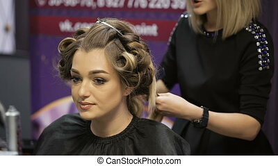 Woman in a beauty salon. Hairstyle for beautiful blonde