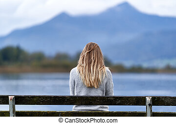Woman in a bench facing the lake