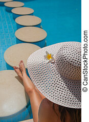 Woman in a big white hat sits on the edge of the pool with stones