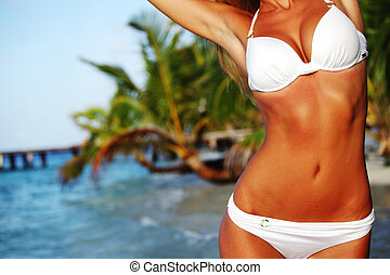 woman in a bikini on a background of palm trees