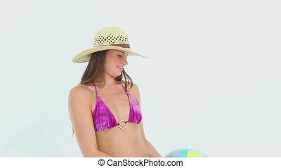 Woman in a bikini playing with a earth ball