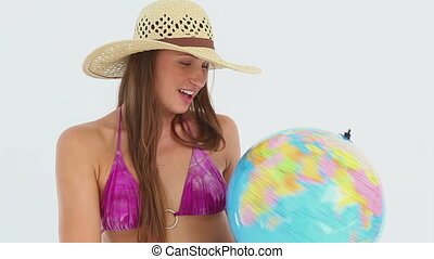 Woman in a bikini spinning a globe