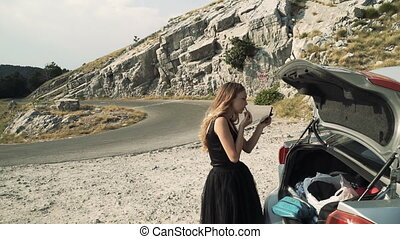 woman in a black dress doing makeup on the side of the road