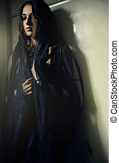 woman in a black robe at green wall