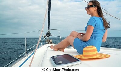 Woman in a blue dress rests aboard a yacht on summer season at ocean. Slow motion
