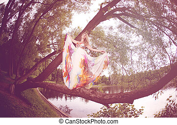 Woman in a bright dress flying in the forest