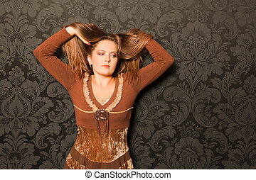 woman in a brown dress standing beside a wall. raised her hands holding her hair. thinks. black and gray pattern on the wallpaper wall.