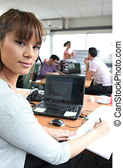 Woman in a busy office using a laptop and headset