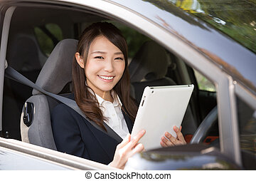 woman in a car - Beautiful young asian woman using tablet...