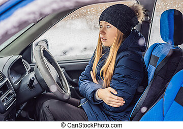 Woman in a car during a snowfall, problems on the road