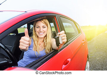 Woman in a car - Happy girl in red car showing thumb up and...