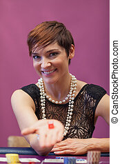 Woman in a casino holding dices