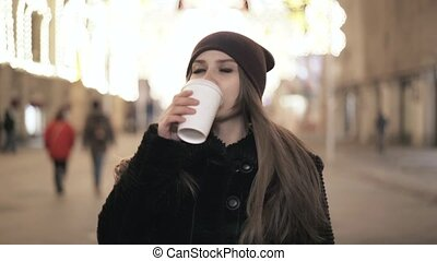 Woman in a coat drinking coffee at night city street