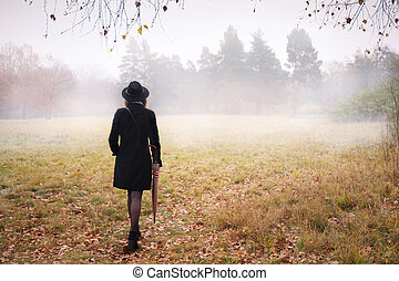 Woman in a coat in foggy weather