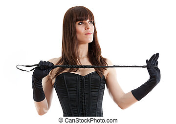 woman in black corset on a white background holds a riding crop