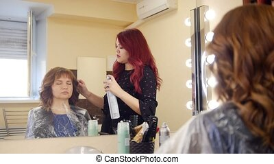 Woman in a cosmetology clinic. Specialist spraying womens...