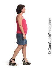 woman in a denim skirt walking on white background
