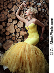 Woman in a dress on background of firewood.
