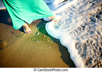 woman in a dress tries the sea with her legs.