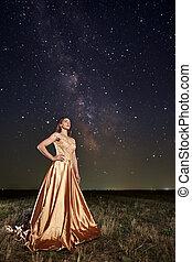 Woman in a dress under Milky Way
