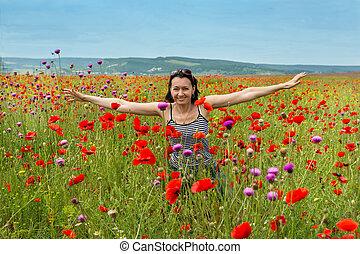 Woman in a field of blooming poppy