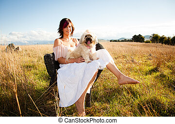 Woman in a field with a poodle on her lap