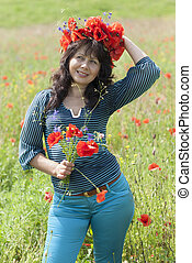 Woman in a field with poppy flowers.