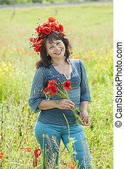Woman in a field with poppy flowers.