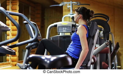 Woman in a fitness room on an exercise bike.