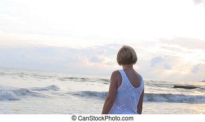 Woman in a gazebo watching sunset