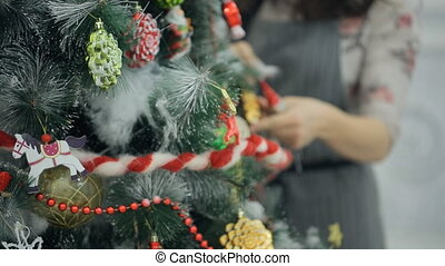 Woman in a gray dress is decorated artificial Christmas tree.