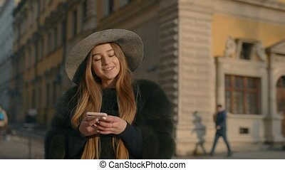 Woman in a gray hat standing in the crowded city street and using her phone for texting