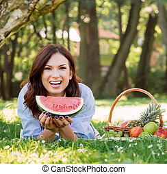 Gorgeous woman in a great mood having a slice of a watermelon in the park.