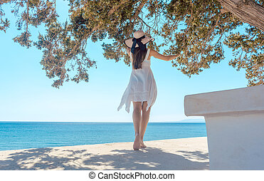 Woman in a greek vacation looking at the ocean