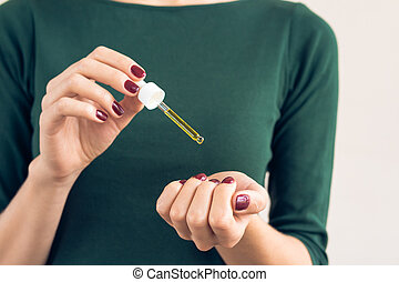 Woman in a green T-shirt and a maroon manicure apply oil to...