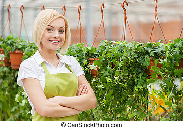 Woman in a greenhouse. Beautiful young woman in apron keeping arms crossed and looking at camera while standing in a greenhouse