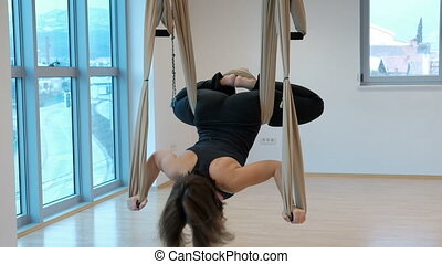 Woman in a hammock doing yoga asana in the lotus position upside down.