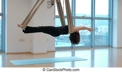 Woman in a hammock for yoga swings in an extended body. The...