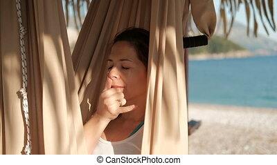 Woman in a hammock on the beach yoga breathing alternate breathing.