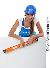 Woman in a hard hat with a laser level and a board left blank for your message
