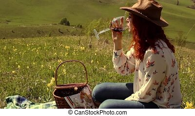 woman in a hat drinking wine sitting on a green meadow high in the mountains
